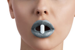 Woman with pill between lips Stock Images