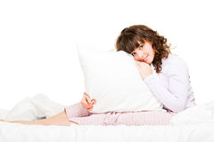 Woman with pillow. Portrait of young woman with pillow in bed Stock Images