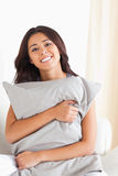 Woman with pillow in her arms. In livingroom Royalty Free Stock Photography