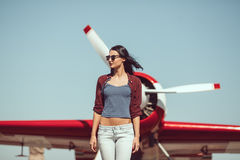 Woman pilot and airplane. Pilot woman next to propeller plane outdoors in sunny day. Attractive young multi-racial Asian Caucasian sexy girl in jeans and shirt Royalty Free Stock Photo