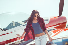 Woman pilot and airplane. Pilot woman standing at cabin plane outdoors in sunny day. Attractive young multi-racial Asian Caucasian sexy girl in jeans and shirt Stock Images