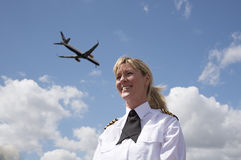 Woman pilot with passenger jet in the sky Royalty Free Stock Photography