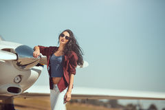 Woman pilot and private business airplane. Pilot woman next to propeller of small private business plane outdoors in sunny day. Attractive young multi-racial Stock Images