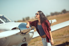 Woman pilot and private business airplane. Pilot woman next to propeller of small private business plane outdoors in sunny day. Attractive young multi-racial Royalty Free Stock Photo