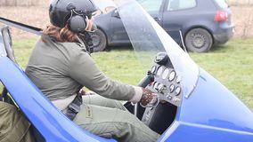 Woman pilot put the key contact at gyrocopter. Pilot put the key contact to start the engine of gyrpcopter stock video
