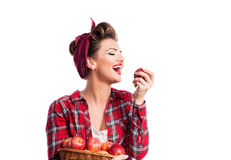 Woman, pin-up hairstyle holding basket, eating apple. Autumn har Stock Images