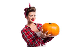 Woman with pin-up hairstyle holding orange pumpkin. Autumn harve Royalty Free Stock Images