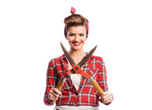 Woman with pin-up make-up and hairstyle holding pruning shears Royalty Free Stock Photos