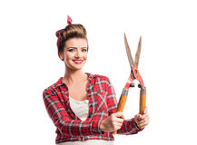 Woman with pin-up make-up and hairstyle holding pruning shears Stock Images