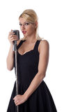 Woman pin-up portrait in black with microphone stock photo