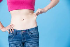 Woman pinch her belly. On the blue background Stock Image