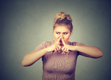 Woman pinches nose with fingers hands looks with disgust something stinks bad smell. Closeup portrait woman pinches nose with fingers hands looks with disgust stock photos