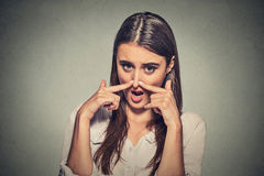 Woman pinches nose with fingers hands looks with disgust something stinks Royalty Free Stock Photo