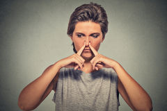 Woman pinches nose with fingers looks with disgust away something stinks bad smell. Headshot woman pinches nose with fingers hand looks with disgust away Royalty Free Stock Image