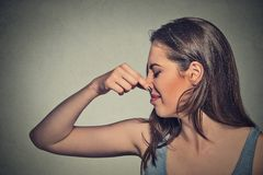 Woman pinches nose with fingers looks with disgust away something stinks Royalty Free Stock Photos