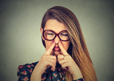 Woman pinches nose with fingers looks with disgust bad smell. Closeup portrait headshot woman pinches nose with fingers hands looks with disgust something stinks Royalty Free Stock Photography