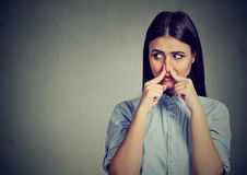 Woman pinches nose with fingers looks with disgust sideway something stinks bad smell. Woman pinches nose with fingers looks with disgust away something stinks stock photo