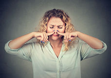 Woman pinches nose with fingers looks with disgust something stinks. Closeup portrait woman pinches nose with fingers looks with disgust something stinks bad royalty free stock images