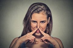 Woman pinches nose with fingers looks with disgust something stinks Royalty Free Stock Photos