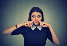 Woman pinches nose looks with disgust something stinks bad smell. Closeup portrait woman pinches nose with fingers looks with disgust something stinks bad smell royalty free stock photos