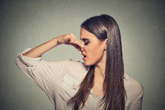 Woman pinches nose looks with disgust something stinks bad smell. Side profile portrait headshot woman pinches nose with fingers looks with disgust away Royalty Free Stock Photography