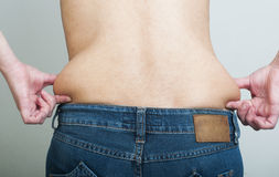 Woman pinching fat from her waist. Back shot Royalty Free Stock Photos