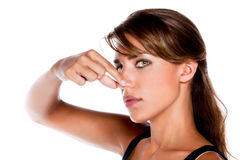 Woman Pinching Nose. An attractive young woman pinches her nose because something smells royalty free stock image