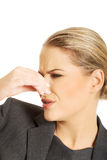Woman pinching nose because of smell Stock Photo