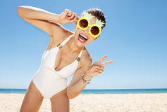 Woman in pineapple glasses showing victory gesture at beach Stock Images