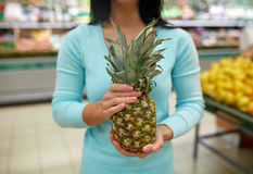 Woman with pineapple at grocery store Royalty Free Stock Images