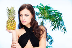 Woman and pineapple. Pretty dark hair woman holding pineapple in front of a palm tree Royalty Free Stock Images