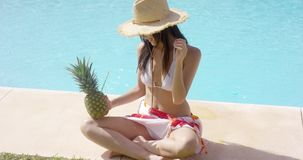 Woman with pineapple and straw hat sits by pool stock footage