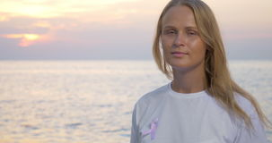 Woman with pink awareness ribbon by the sea. Young blond woman in white t-shirt wearing pink breast cancer awareness ribbon. She looking at the sea and then stock footage