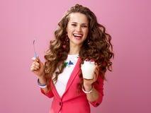 Woman on pink background with farm organic yogurt and spoon. Pink Mood. smiling trendy woman with long wavy brunette hair on pink background with farm organic Stock Photos