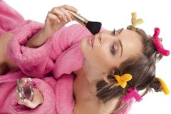 Woman in pink bath robe making-up Stock Images