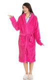 Woman in pink bathrobe pointing aside. Royalty Free Stock Images