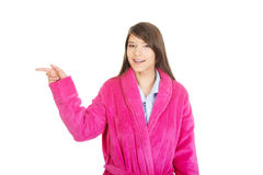 Woman in pink bathrobe pointing aside. Stock Images