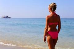 Woman in pink bikini standing on the beach Royalty Free Stock Image