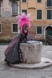 Masked woman in pink and black hand made costume with fan and ornate painted feathered mask at Venice Carnival stock photos