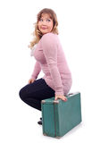 Woman in pink blouse sits on suitcase Royalty Free Stock Photography