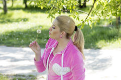 The woman in the pink blows on a dandelion Royalty Free Stock Images