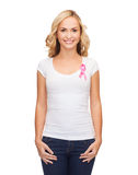 Woman with pink cancer awareness ribbon. Healthcare and medicine concept - woman in blank t-shirt with pink breast cancer awareness ribbon royalty free stock photos