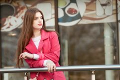 Woman in pink coat waiting bye at the window of the restaurant Royalty Free Stock Photos