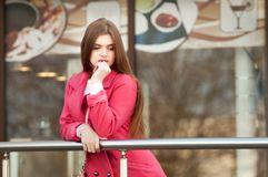 Woman in pink coat waiting bye at the window of the restaurant Stock Photos