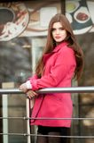Woman in pink coat waiting bye at the window of the restaurant Royalty Free Stock Photography