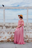 Woman in Pink Cold Shoulder Long Dress Sitting on Grey Concrete Bench Under Black Bird Royalty Free Stock Photography
