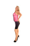 Woman in pink corset. A slim lovely young woman in a pink corset and black skirt standing in profile for white background royalty free stock photos