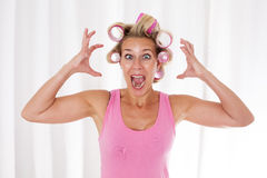 Woman with pink curlers. Blond woman with pink curlers is screaming stock image