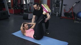 Woman in pink doing leg raises with a personal coach stock footage