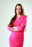 Woman in pink dress with arms folded standing Stock Photo